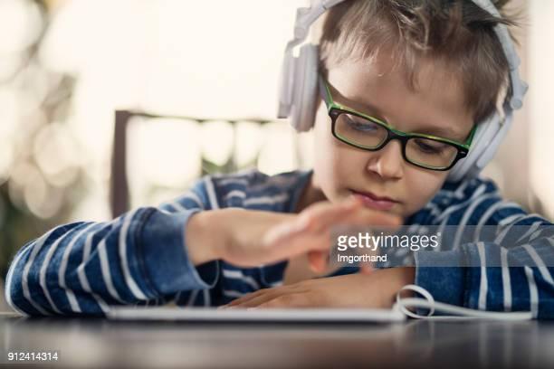 Little boy in headphones listening to music using talet