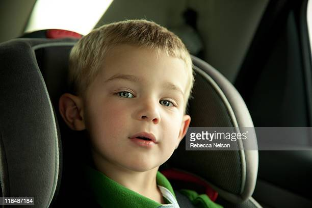 Little boy in his in the car strapped into carseat