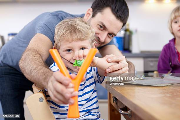 Little boy in kitchen learning to use slingshot