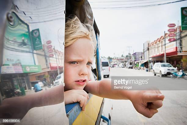 Little boy (3-4) in open taxi