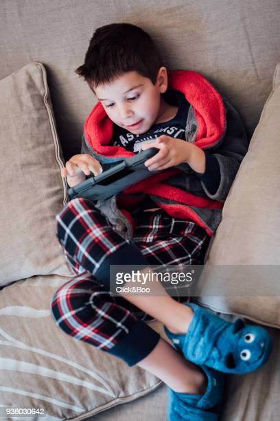 Little boy in pajamas playing with a tablet