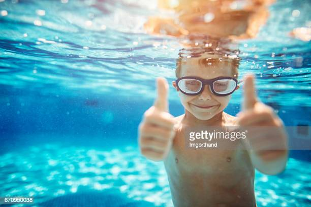 little boy in pool showing thumbs up - piscina foto e immagini stock
