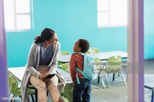 little boy in preschool, talking to teacher - teacher stock pictures, royalty-free photos & images