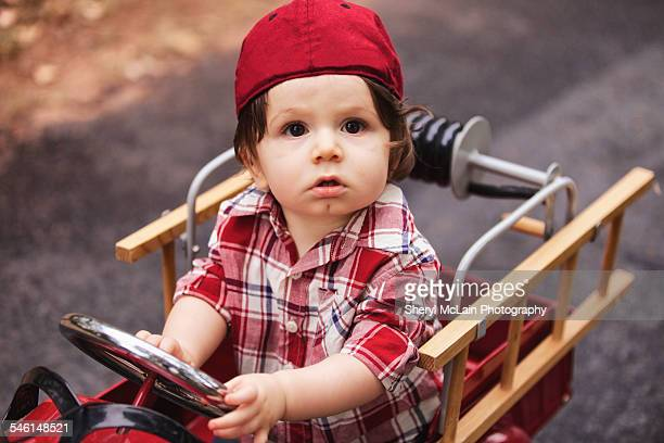 Little Boy in Red Firetruck Looking at Camera