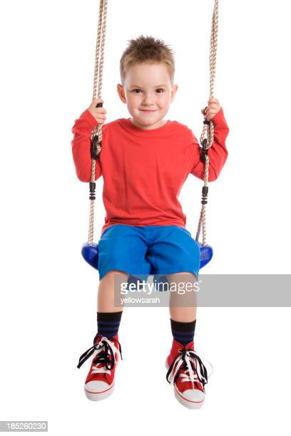 Little boy in red shirt and blue shorts on a swing