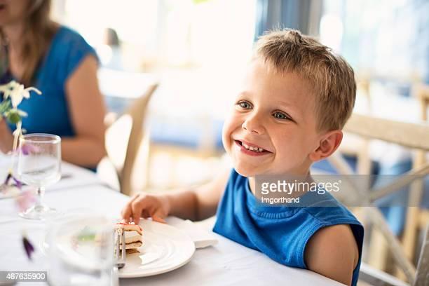 Little boy in restaurant eating a delicious dessert
