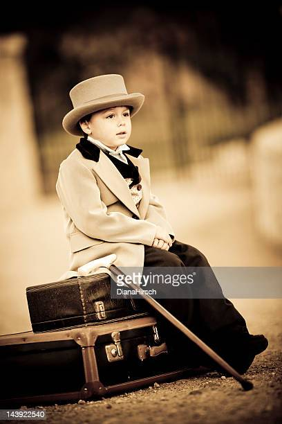little boy in retro style waiting with old baggage