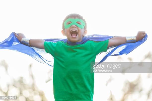 Kleiner Junge in Superhelden-Kostüm bereitet sich für Schlacht