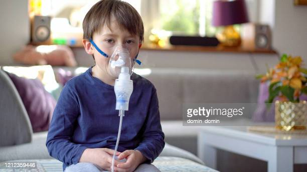little boy in the inhalation mask with breathing troubles - respiratory disease stock pictures, royalty-free photos & images