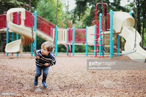little boy in the playground on the swing - menino loiro olhos azuis imagens e fotografias de stock
