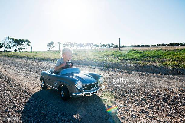 little boy in toy car on country road - toy car stock pictures, royalty-free photos & images