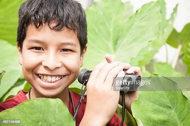 Petit garçon dans un climat tropical Explore en plein air à l'aide de jumelles.