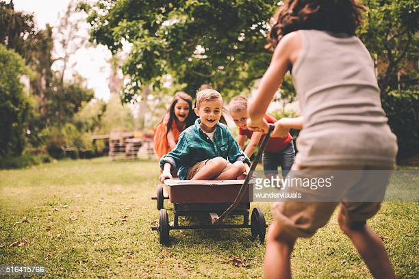 Little boy in wagon being pushed and pulled by friends
