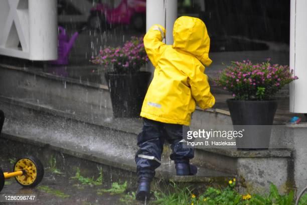 little boy in yellow rainwear running across the yard through pouring rain. raindrops splashing down on stair step. - レインブーツ ストックフォトと画像