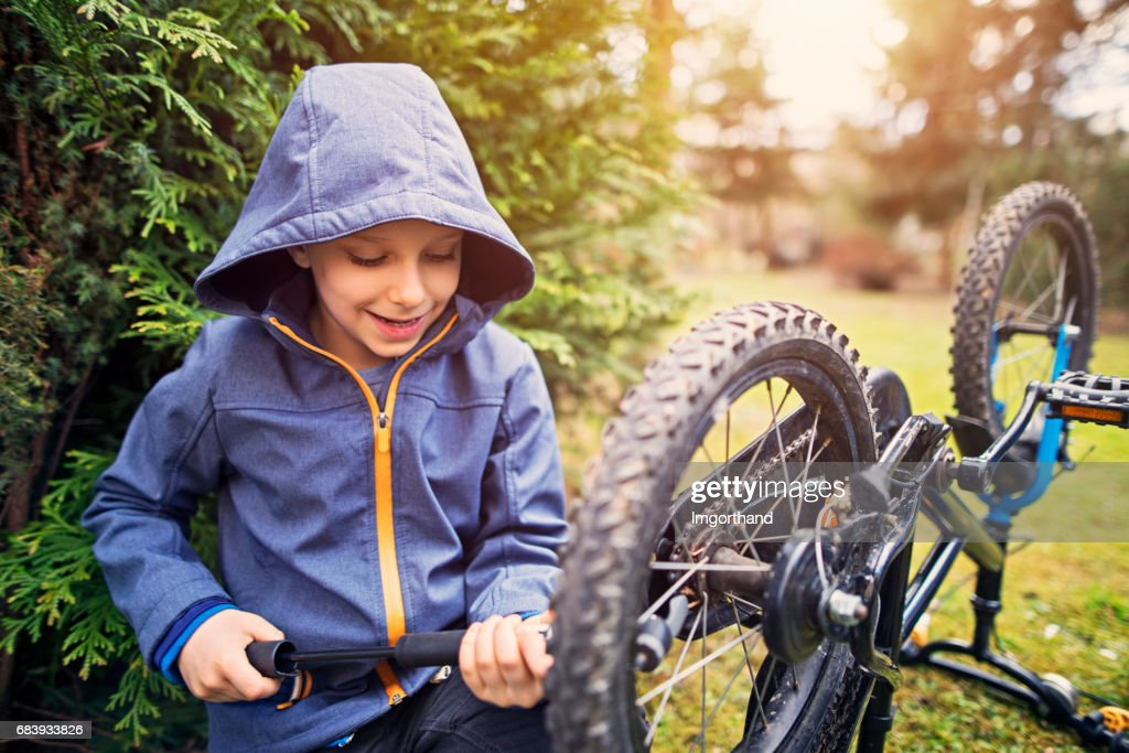 Little boy inflatingf bicycle tires : Stock Photo