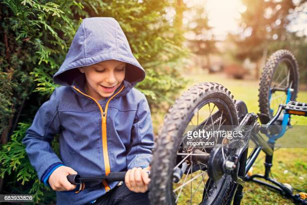 little boy inflatingf bicycle tires - air pump stock photos and pictures