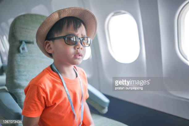 little boy inside airplane during summer holiday - toddler at airport stock pictures, royalty-free photos & images