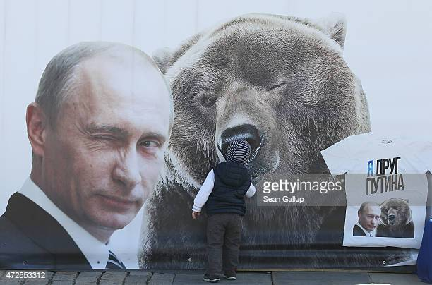 A little boy inspects a billboard showing a winking Russian President Vladimir Putin and a bear as well as a tshirt that reads 'I'm a friend of...