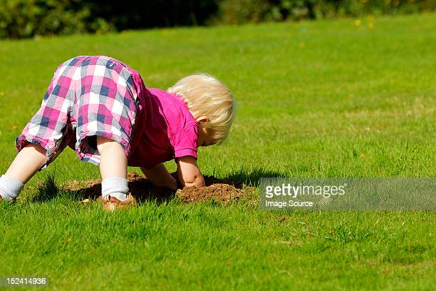 Little boy investigating molehill