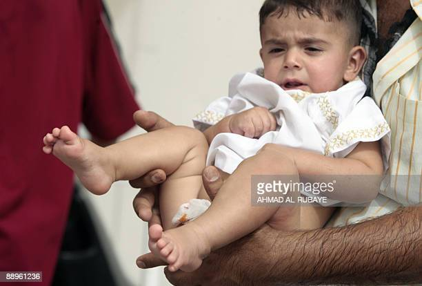 A little boy is carried away following his circumcision operation in the eastern Baghdad district of Sadr City on July 10 2009 Two hundred boys were...