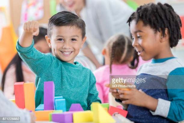 little boy is grateful for playtime with friend at school - childcare stock pictures, royalty-free photos & images