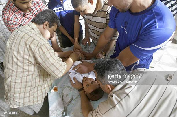 A little boy is held down as he undergoes circumcision in the eastern Baghdad district of Sadr City on July 10 2009 Two hundred boys were circumcised...