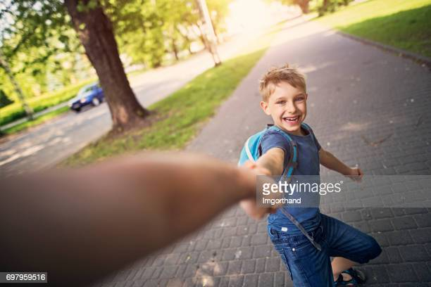 little boy is pulling his father to city park. - personal perspective stock pictures, royalty-free photos & images