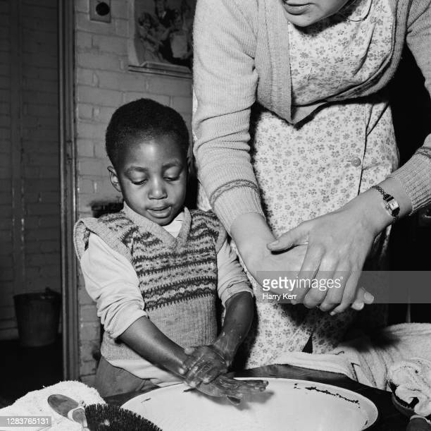 Little boy is taught to wash his hands properly at the Brixton Day Nursery on Coldharbour Lane in Brixton, south London, 1955. Four years earlier...