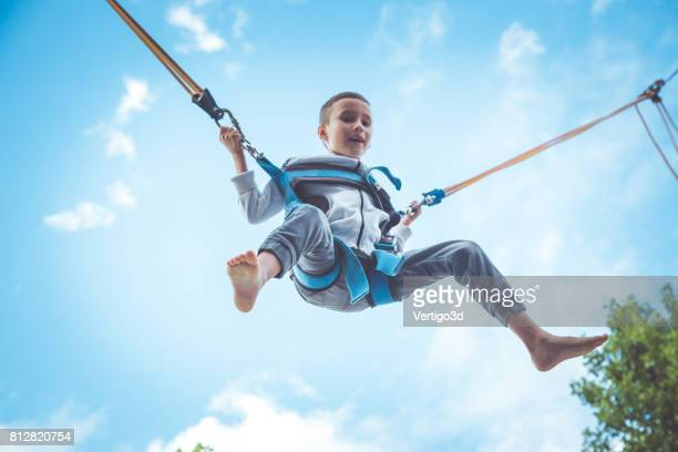 Little boy jumping at trampoline