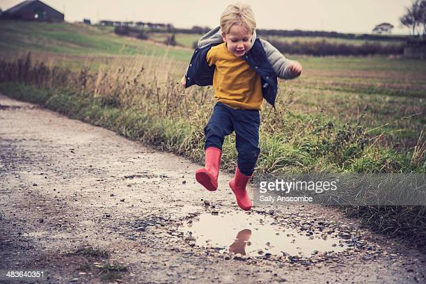 Little boy jumping in a muddy puddle