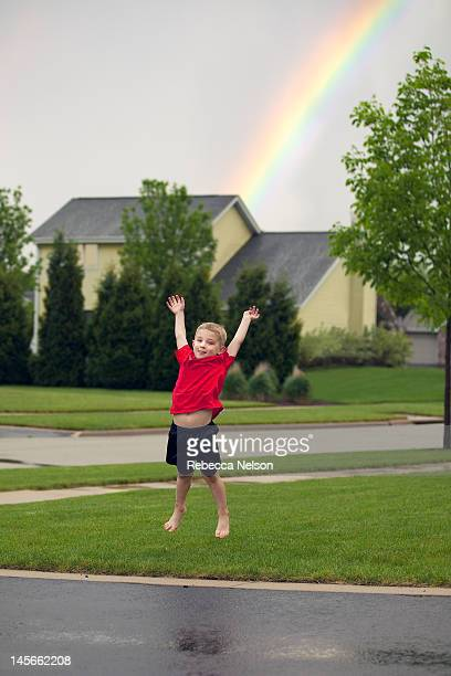 Little boy jumping in midair with rainbow in sky