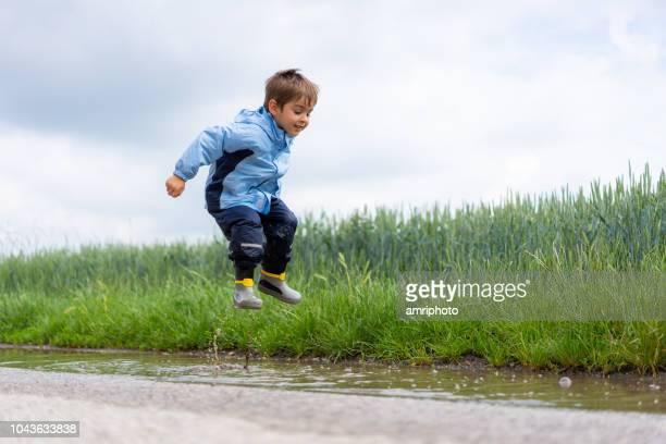niño saltando en un charco de agua - gabardina ropa impermeable fotografías e imágenes de stock