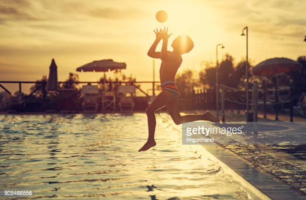 little boy jumping into swimming pool - catching stock pictures, royalty-free photos & images