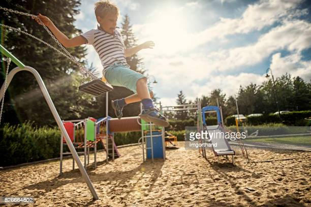 little boy jumping off the swing - danger stock photos and pictures