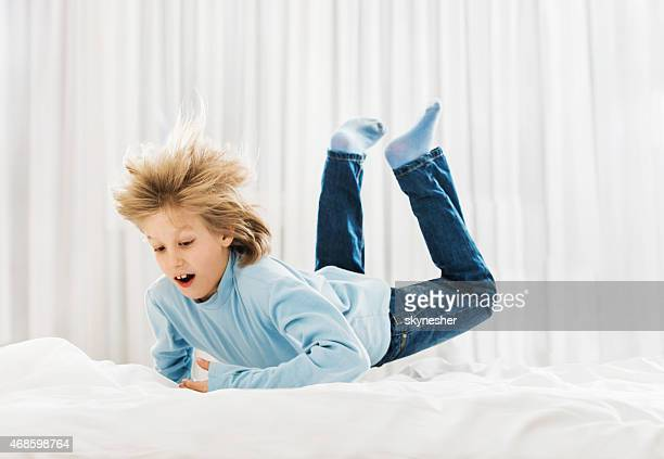 Little boy jumping on bed.