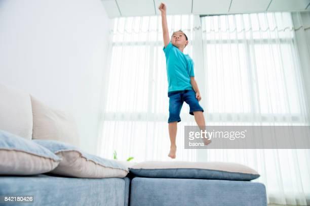 Little boy jumping on sofa