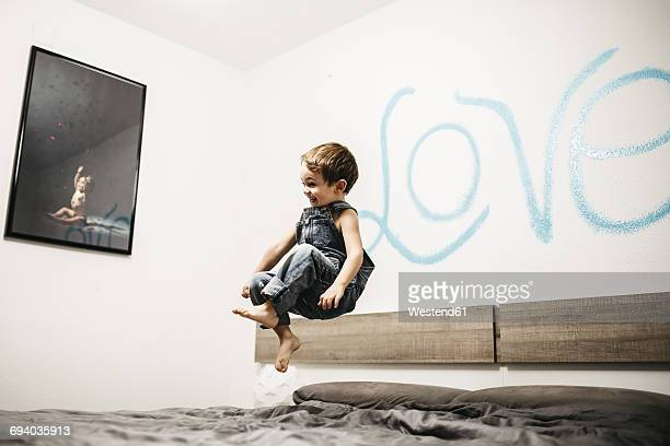 Little boy jumping on the bed of his parents