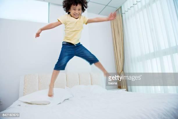 Petit garçon sauter sur le lit