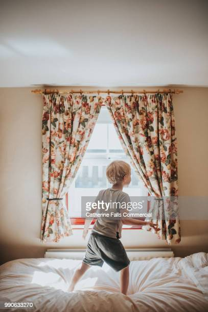 little boy jumping on the bed - only boys stock pictures, royalty-free photos & images
