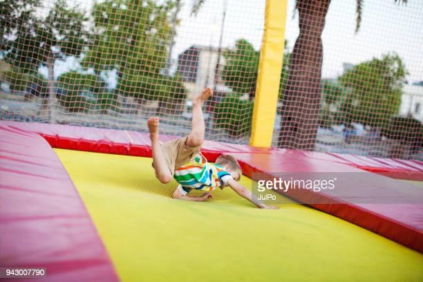 Liten pojke hoppar på studsmatta