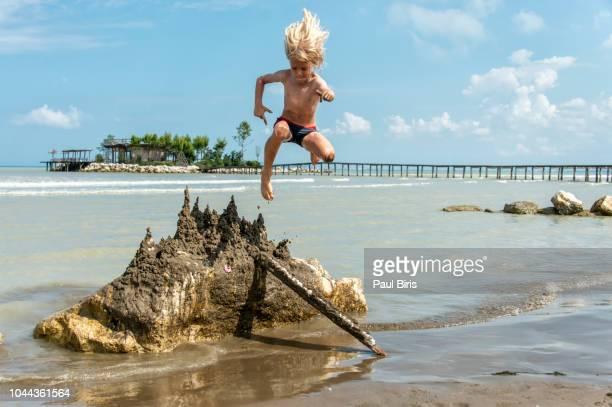 little boy jumping over a sand castle , near durres, albania - durazzo foto e immagini stock