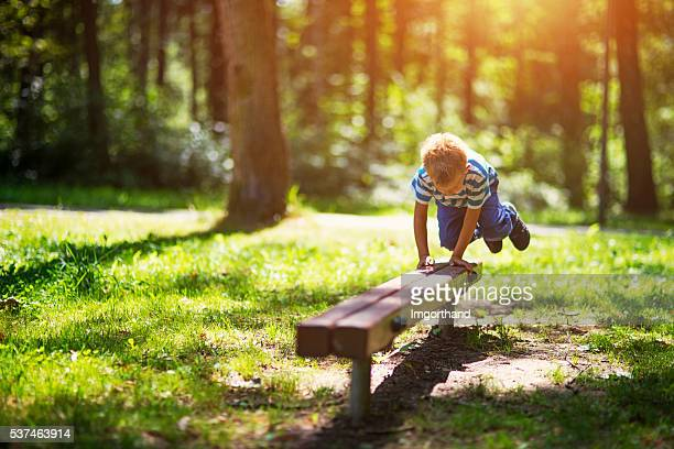 Little boy jumping over bench in sunny park