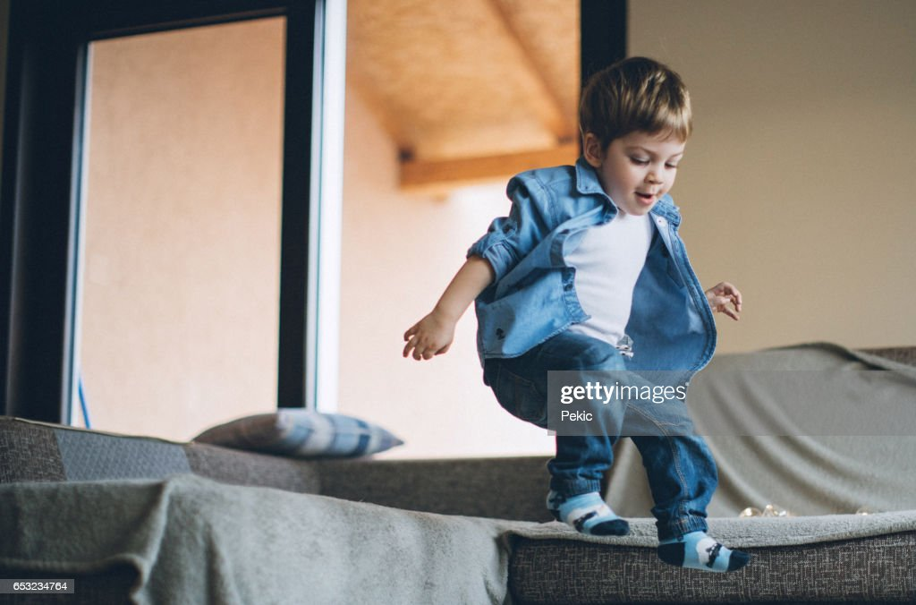 Little boy jumping with joy on sofa : Stock Photo
