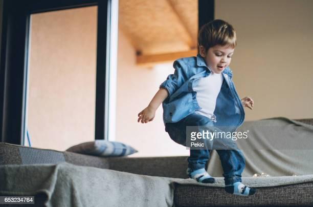 少年の喜びでソファの上にジャンプ