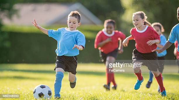 Little Boy Kicks Soccer Ball to Goal