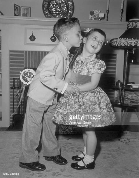 Little boy kisses little girl while he has a Valentine gift behind his back 1939