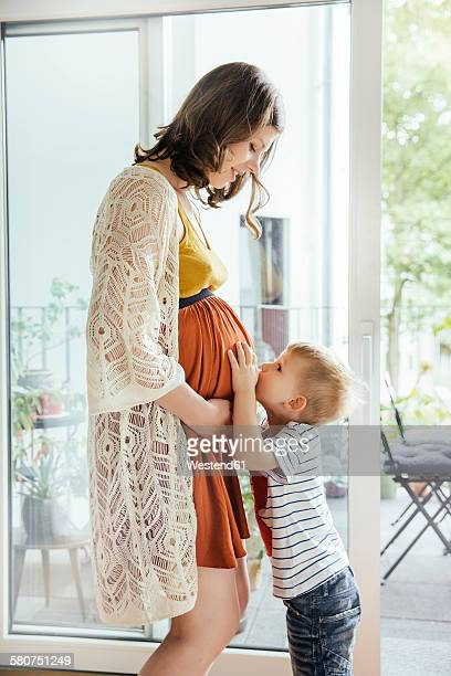 Little boy kissing belly of his pregnant mother at home