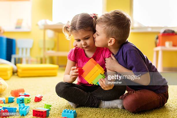 Little boy kissing girl who is playing with toy blocks.