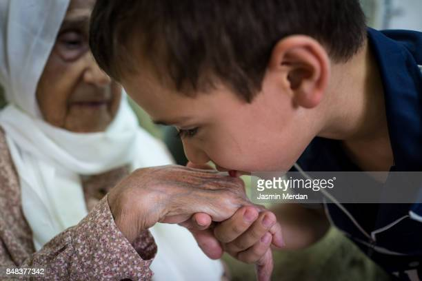 Little boy kissing Grandmother hand