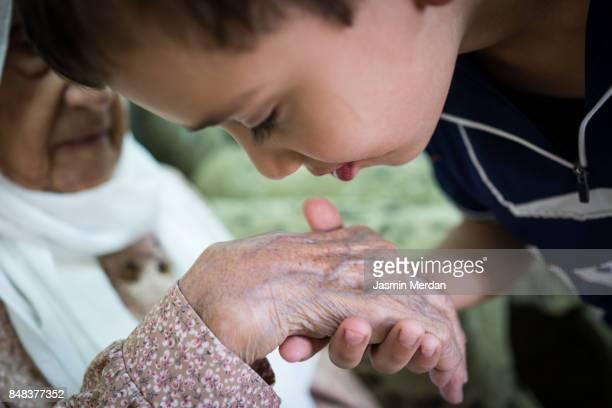 Little boy kissing Grandmother hand